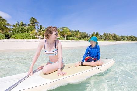 Positiver lächelnder Junge im Rashguard und seine junge Mutter, die genießen, stehen oben paddleboarding, aktives gesundes Familienferienkonzept, Weitwinkelschuß Standard-Bild - 87911058