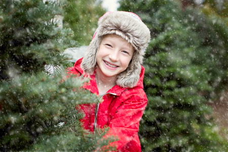 excited little boy choosing christmas tree at the market while snowing, winter holiday concept