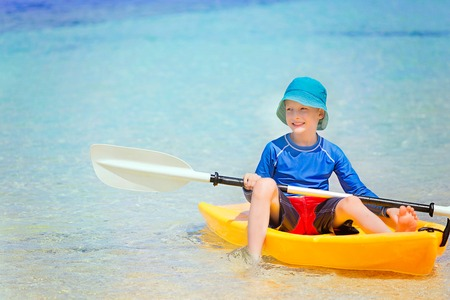 cute smiling little boy in the kayak holding paddle enjoying active vacation at the tropical island at fiji, south pacific, copy space on the left