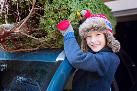 happy smiling boy christmas tree shopping, taking the tree off car roof, enjoying magical time Stock Photo