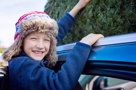 happy smiling boy christmas tree shopping, taking the tree off car roof, enjoying magical time Imagens