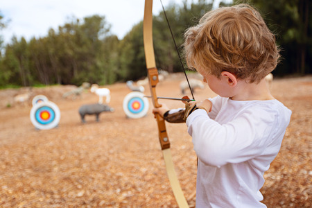 little boy doing archery, aiming at the target, fun outdoor activity concept Archivio Fotografico
