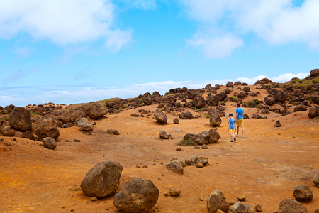 family of two, father and son, hiking in keahiakawelo, beautiful rock garden at lanai island, hawaii, family active vacation concept