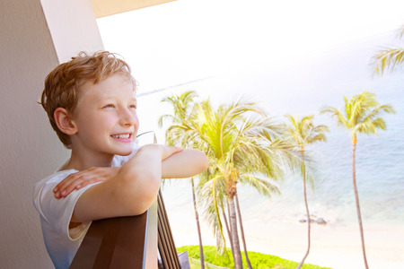 positive smiling boy enjoying tropical vacation at maui island, hawaii, palm trees in the background, summer vacation concept