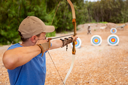 giovane che fa tiro con l'arco, mirando al bersaglio, divertente attività all'aperto concept