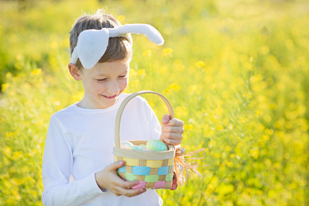 cute cheerful child wearing bunny ears and holding colorful basket full of easter eggs enjoying easter egg hunt at blooming flowers field, easter holiday concept, copy space on right Stock Photo - 127186632