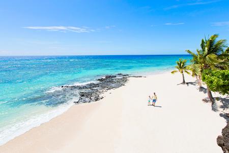 Luftaufnahme des atemberaubend schönen weißen Sandstrandes mit Palmen und türkisfarbener Wasserlagune und zweiköpfige Familie, Vater und Sohn, die gemeinsam den Sommerurlaub auf der Insel Fidschi genießen, Familienurlaubskonzept
