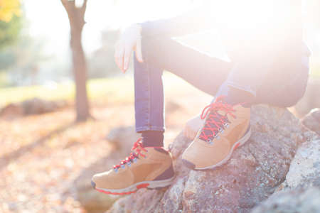 close-up view of boy's legs in trekking boots, child sitting on a rock with no face visible due to sun glare, active healthy lifestyle concept
