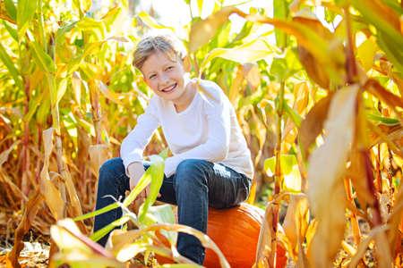 smiling poisitve boy sitting on a pumpkin in corn maze at pumpkin patch, fall season concept