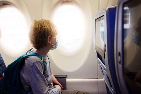 boy wearing face mask sitting in airplane cabin, travel during coronavirus pandemic concept