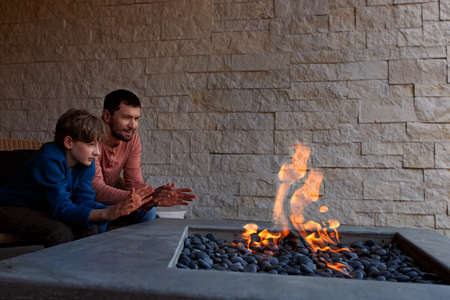 view of firepit and happy smiling family of two, father and son, warming their hands by the fire and enjoying time together