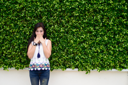 gag: Portrait of lady standing and Hands gag action with Wearing a white shirt with jeans And wearing a watch on The background is green leaf Stock Photo