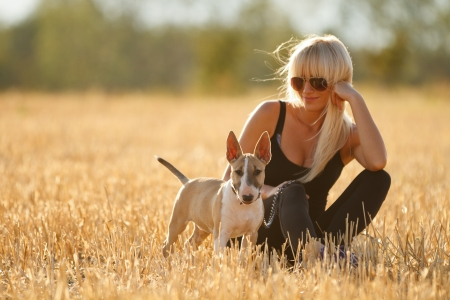 Beautiful blonde girl with English bull terrier puppy Stock Photo