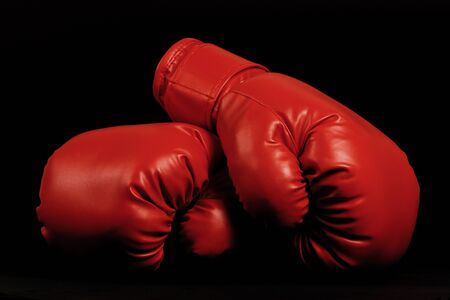 boxing glove: A pair of dark red vintage boxing gloves on black background