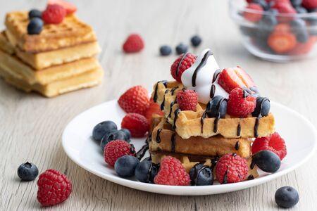 Belgian waffles with fresh fruits on wooden backgroun Archivio Fotografico