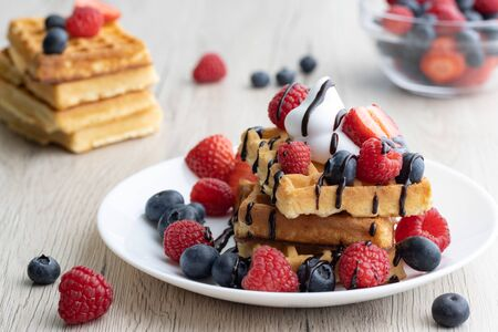 Belgian waffles with fresh fruits on wooden backgroun Banque d'images