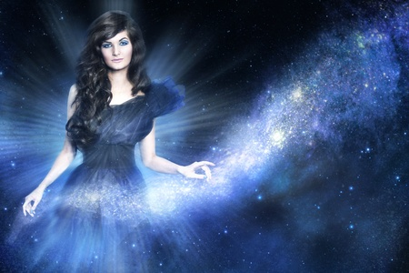 Beautiful woman as galaxy godness holding a milky way on blue background photo