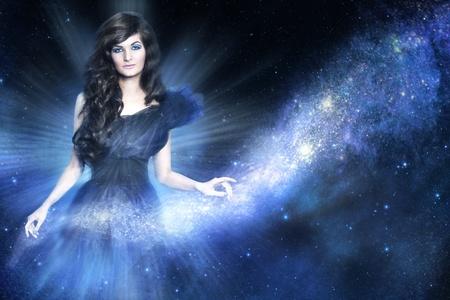 Schöne Frau als Göttin, die eine Galaxie Milchstraße auf blauem Hintergrund
