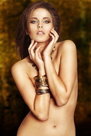 junge nackte mädchen: Sexy junge Frau mit goldenem Make-up und Armbänder auf goldenem Hintergrund