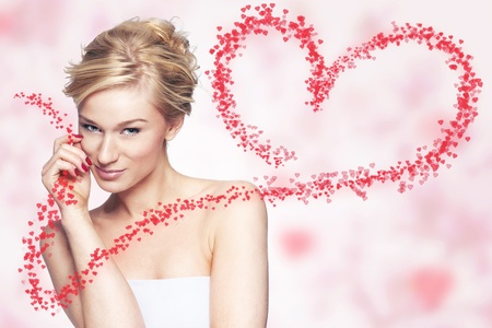 Young woman holding flying hearts on pink background photo