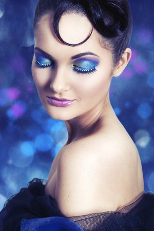fantasy makeup: Young woman with blue-purple make up on bokeh backgroung