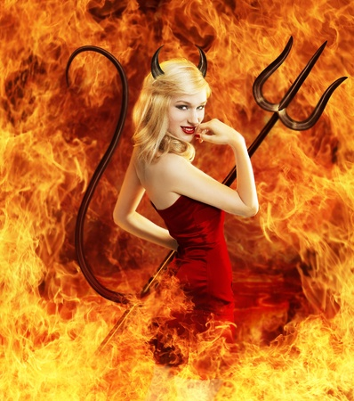 Sexy young blond woman in red dress as devil in fire with horns, tail and trident Stock Photo - 11957892