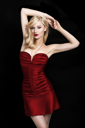 above head: Sexy young blond woman in a red dress on a black background with her hands above the head