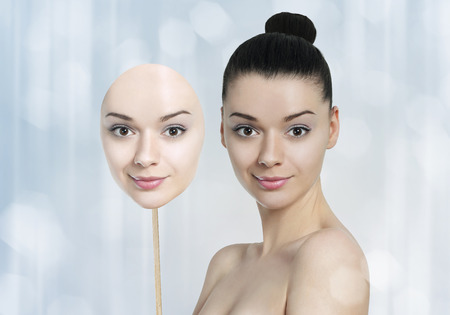 Beautiful young woman with dark skin and light skin face mask-skin whitening concept Stock Photo