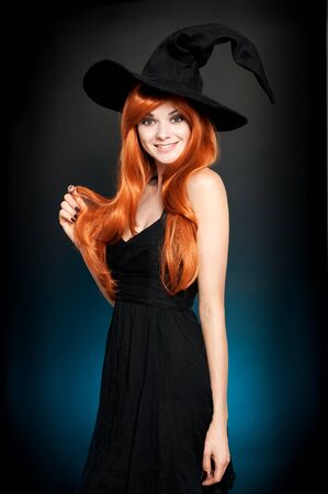 sexy glamour: Beautiful young woman as halloween witch with scroll-magical portrait