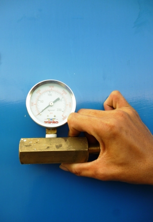 One hand holds a male part of a regulator and wrench It is isolated on a blue background  photo