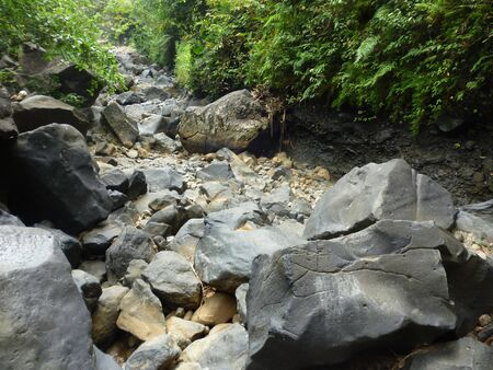 tumbled: river rocks in a stream waterfall in Jepara, Indonesia Stock Photo