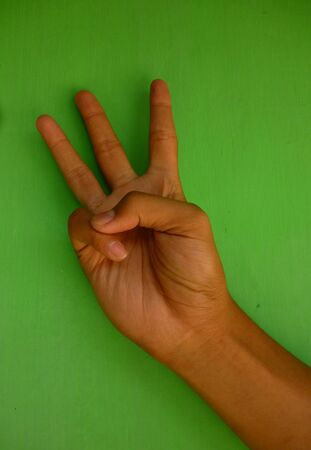 express positivity: Male hand perfect gesture isolated on green background Stock Photo