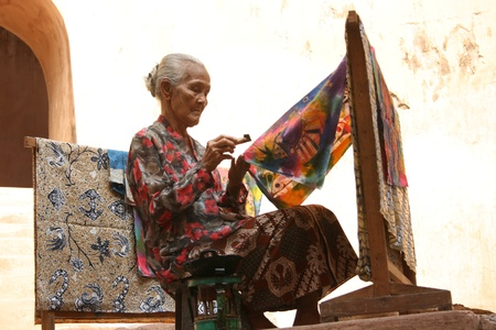 indonesia people: YOGYAKARTA-SEPTEMBER 14  An elderly woman making traditional batik cloth at the Castle on September 14, 2008 in Yogyakarta