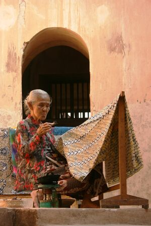 YOGYAKARTA-SEPTEMBER 14  An elderly woman making traditional batik cloth at the Castle on September 14, 2008 in Yogyakarta
