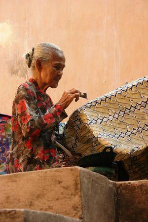 yogyakarta: YOGYAKARTA-SEPTEMBER 14  An elderly woman making traditional batik cloth at the Castle on September 14, 2008 in Yogyakarta