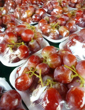 Vacuum packed grape on a fruits market in indonesia photo