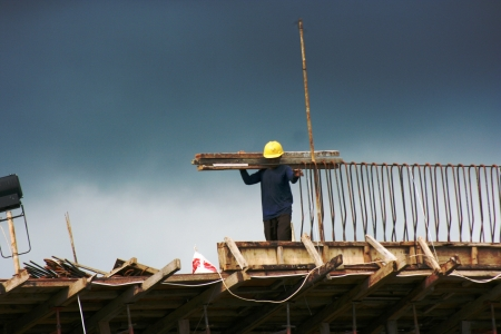 Two ironworkers atop the skeleton of a modern building carrying wood for the pair