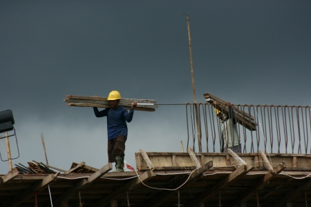 Two ironworkers atop the skeleton of a modern building carrying wood for the pair photo