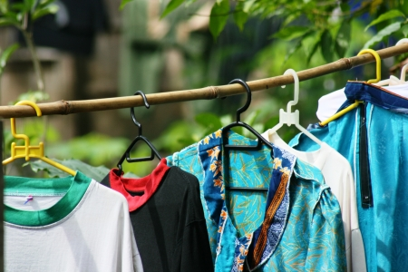 Colorful clothes hanging to dry on bamboo line and sun shining  photo