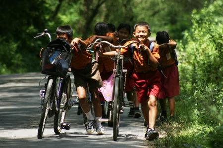 인도네시아의 외진 지역에있는 초등학생들이 자전거를 타다