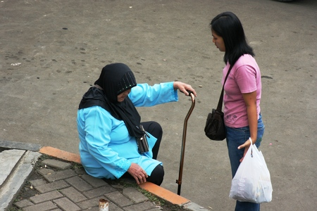 woman helping old indonesian woman walk down street with stick
