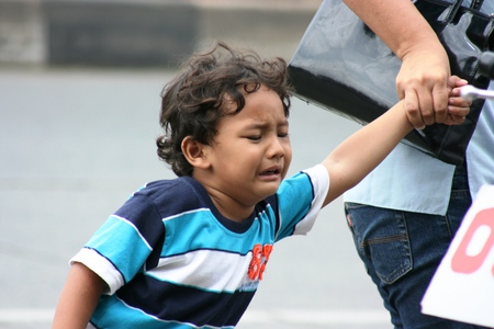 fussy: a child crying in the street because his mother pulled fussy Editorial