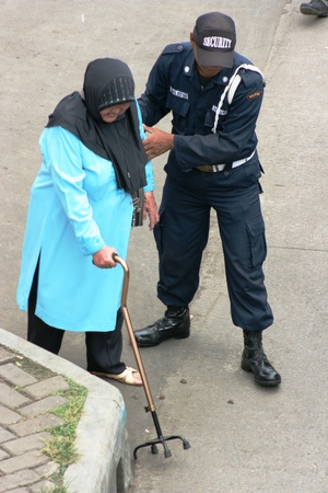 hobble: man helping old indonesian woman walk down street with stick