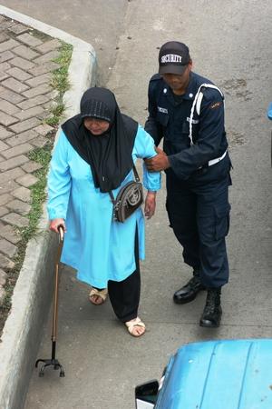 indonesian woman: el hombre ayuda anciana indonesio camina por la calle con bast�n