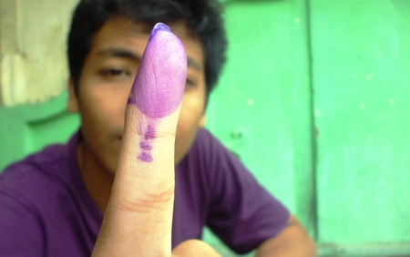 presidential election: young boy dips of one of her fingers into the ink as a sign that she has voted in in Indonesia presidential election, 9 July 2014 Editorial