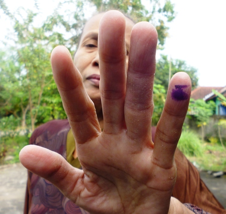 voted: old mother dips of one of her fingers into the ink as a sign that she has voted in in Indonesia presidential election, 9 July 2014 Editorial