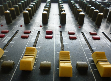 loopable: Side closeup on a sliders of a mixing console. It is used for audio signals modifications to achieve the desired output. Applied in recording studios, broadcasting, television and film post-production Stock Photo