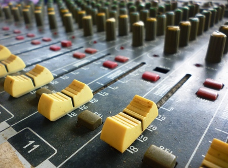 postproduction: Side closeup on a sliders of a mixing console. It is used for audio signals modifications to achieve the desired output. Applied in recording studios, broadcasting, television and film post-production Stock Photo