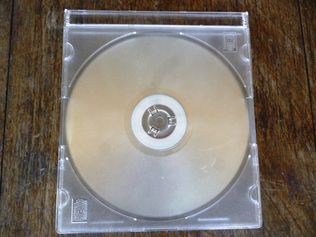 jewel case: CDDVD case with white disc on wood background