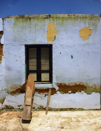 desolated: old abandoned house with grunge wall and window